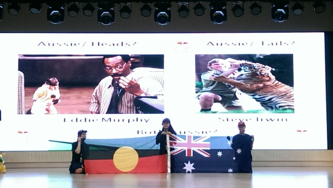 [Australia holding up two flags, with images of Eddie Murphy and Steve Irwin projected onto the screen. Which are Australian?]
