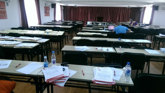 [Papers on tables, at the meeting hall where grading occurs]